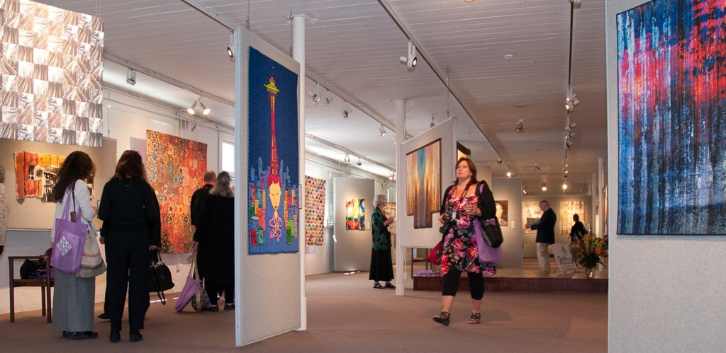 The artists stroll through the Dairy Barn gallery on opening night.