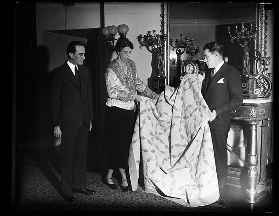 The quilt which won prizes at the World Fair in Chicago is presented to Mrs. Roosevelt by E.J. Condon. L.T. Conway views the ceremony. Both men are connected with a merchandising concern doing business on a nationwiide scale. The prize winning quilt was made by Margaret Rogers Caden of Lexington, KY